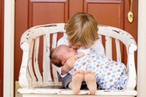 אח גדול מנשק את אחותו התינוקת. מגע הוא אחד הדברים החשובים ביותר בשלושת החודשים הראשונים לחייו של התינוק.